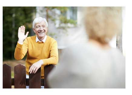 An older man waving at his neighbor outdoors on his porch.