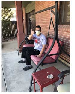 A teenage boy sitting on a swinging settee on his porch, waving.