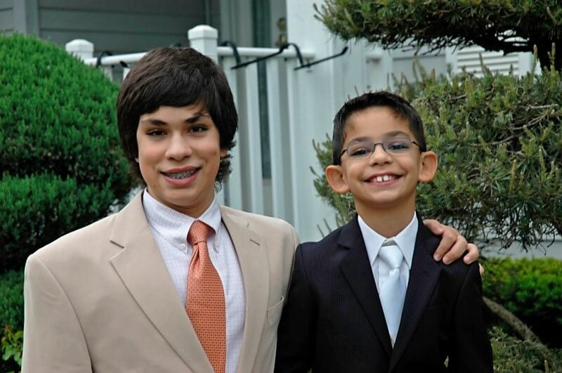 Photo of two young boys, dressed up in suits and ties, affected by Fragile X.
