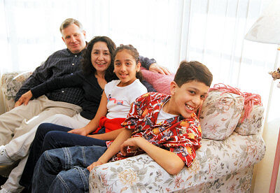 Family of four all sitting on their sofa