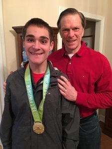 A father and his teenage son who's wearing a medal around his neck