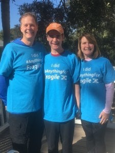 A father, mother, and teenage son wearing matching blue t-shirts that say I did Anything for Fragile X