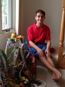 A barefoot teenage boy wearing a t-shirt and shorts, sitting in his bedroom next to a toy.