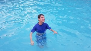 Teenage boy wearing a blue t-shirt and jeans standing in a swimming pool with water up to his waist