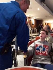 Riley, seated, shaking hands with astronaut Mark Vande Hei at space camp.