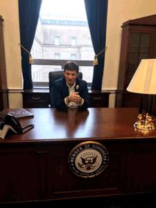 Dillon Kelley behind Member of Congress desk.