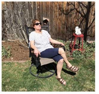 Jayne Dixon Weber in a lawn chair in her backyard, taking in the sunshine.