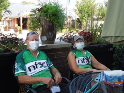 2 participants of the The 5th Annual Bike to X Out Fragile X at a table outdoors.
