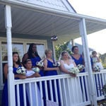 Christine and her bridal party on the front porch of a blue house