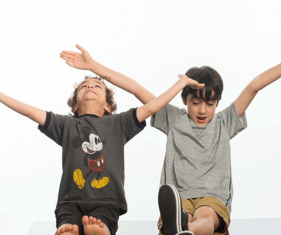Two boys with Fragile X syndrome raising their hands
