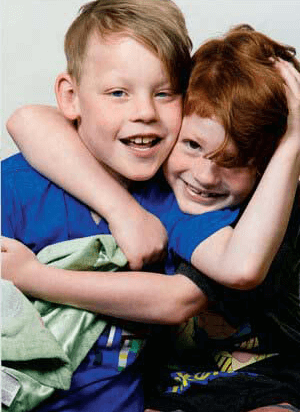 A young boy and girl hugging and smiling