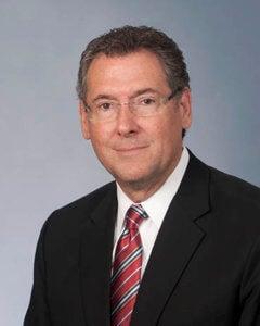Gregg Harper while male wearing dark suite, white shirt, red tie.