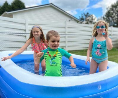 Paige & Mae Otterson in the kiddie pool with their Fragile X superhero brother