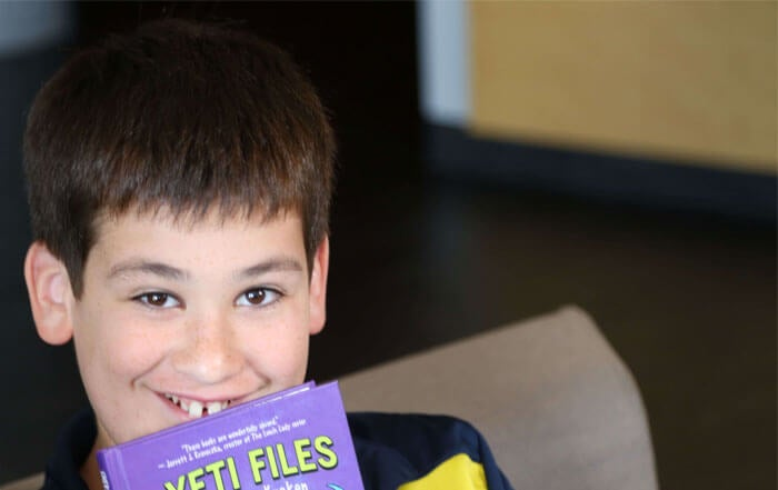 Boy with Yeti Files book, grinning