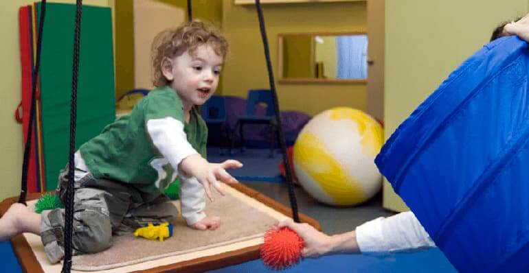 A young male child working with an occupational therapist