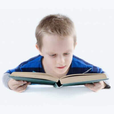 Young short-haired boy in a blue t-shirt holding a book with both hands and reading