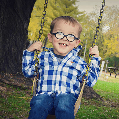 Young boy on a tree swing.