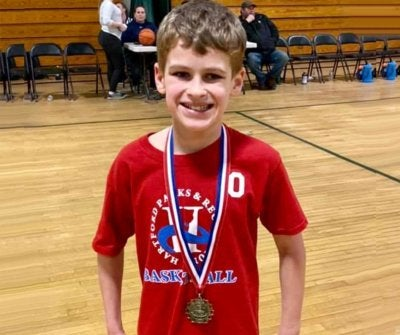 Brayden on a basketball court with a medal around his neck