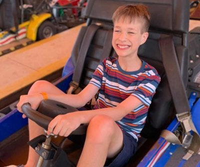 Brayden Crawford in a go cart, wearing shorts and a t-shirt, and a big smile