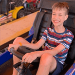 Young thin male riding an amusement park car wearing a t-shirt and shorts and smiling
