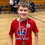Young boy wearing a red t-shirt and a medal around his neck standing on an indoor basketball court