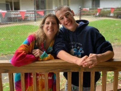 brian and his mom leaning on a fence