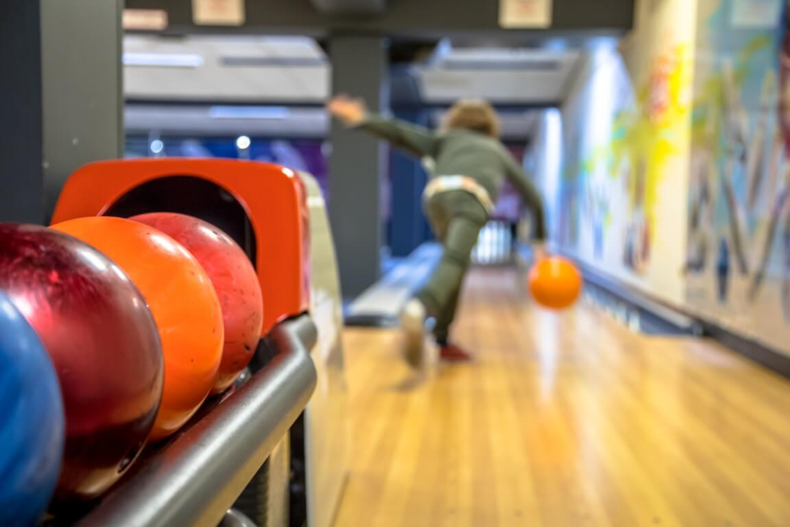 Child throwing bowling ball on indoor bowling alley