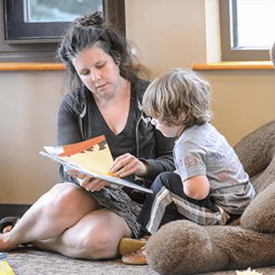 Woman and young boy sitting on the floor looking through book