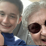Young boy in a blue t-shirt and his grandmother with gray hair wearing sunglasses