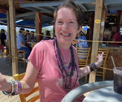 Courtney Laubach at an outdoor cafe, wearing lots of necklaces and bracelets, and smiling