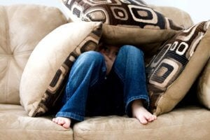 Boy hiding under cushions on a sofa