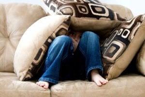 Boy hiding under cushions on a sofa