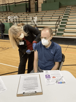 Dr. Erickson at a gymnasium in Indiana receiving his first COVID-19 vaccination from a nurse.