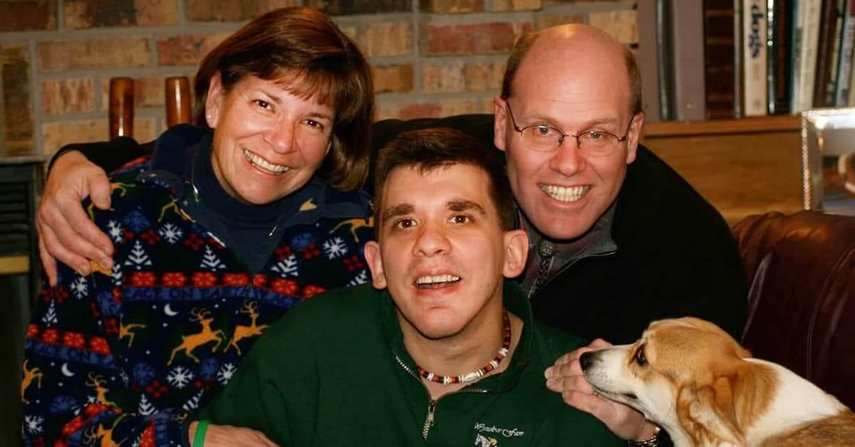 A mom, dad, young adult son, and their dog, at home.