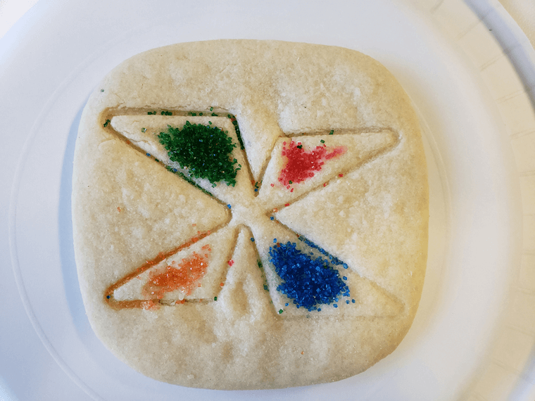 Cookie decorated with imprint of NFXF X logo and colored sprinkles