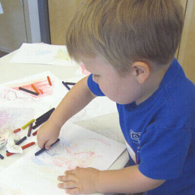 A male blonde toddler holding a crayon at a small table with papers across it