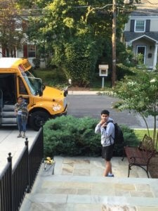 boy leaving home to get on a school bus