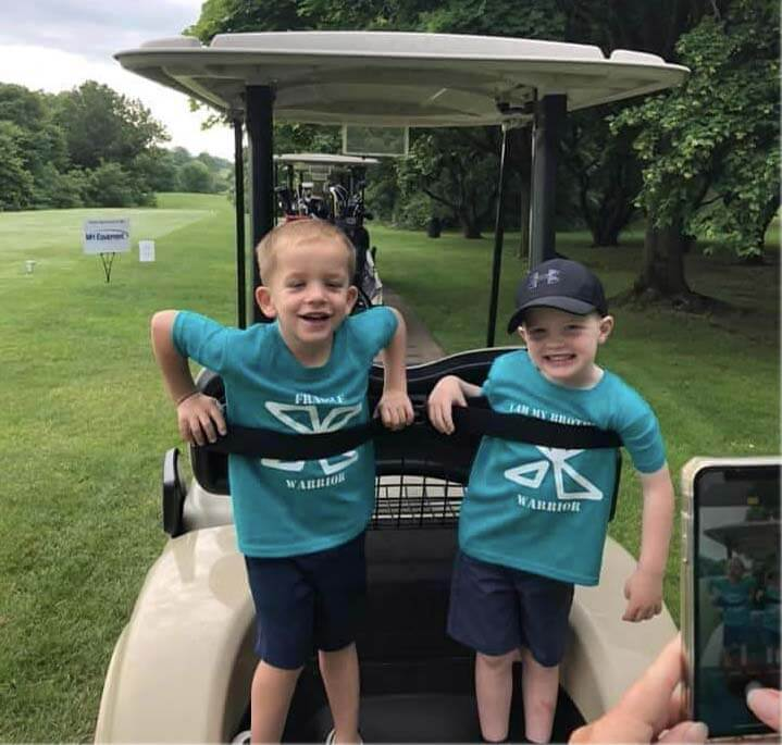 Reid and his brother riding on the back of a golf cart