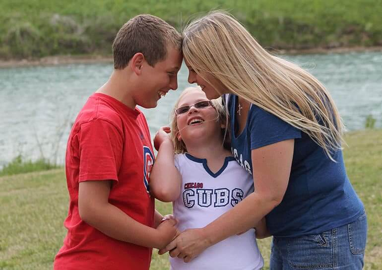 Holly with her son Parker and daughter Allison outdoors in a loving embrace