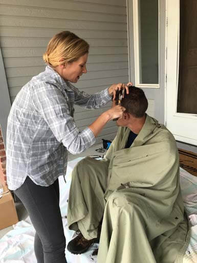 Ian's sister cutting his hair on the porch.