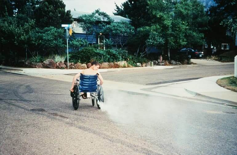 A boy in the street on a wheelchair with a smoking tail pipe.