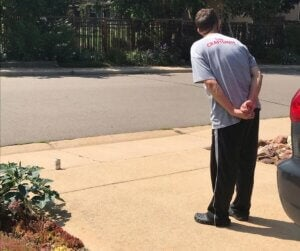 ian waiting for the mail carrier with a soda for them in the driveway