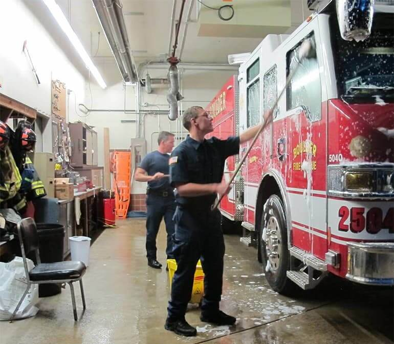 2 men washing a fire truck with long brushes and soap and water