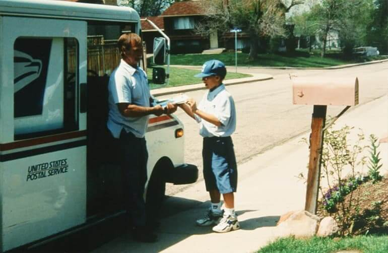 A boy helping a mailman by his truck