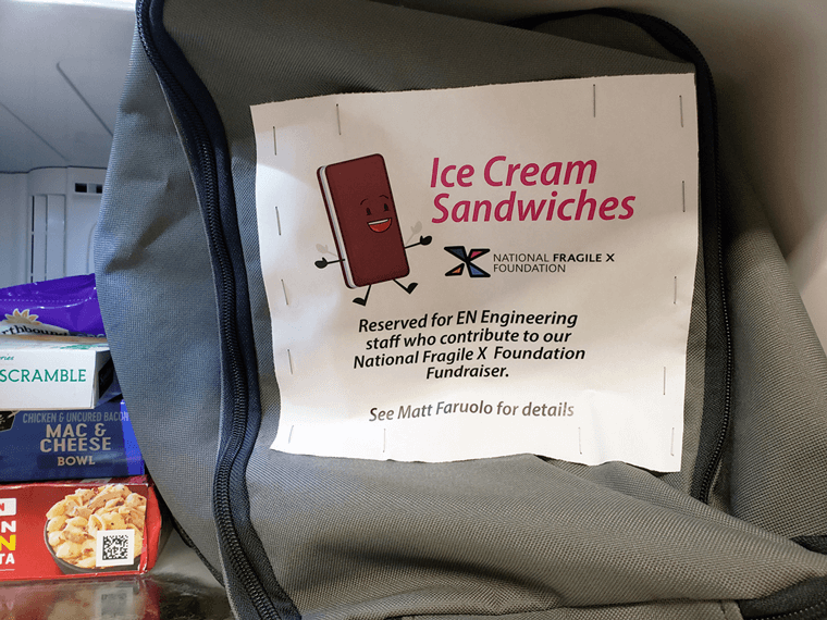 Inside of freezer with bag of ice cream sandwiches and a sign