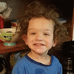 Male toddler with curly hair grinning with food on his face