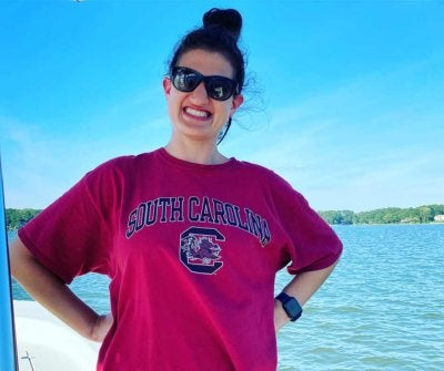 Mallory wearing sunglasses and posing by a lake, smiling big