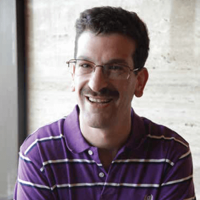 Man in purple shirt, glasses, and a mustache smiling