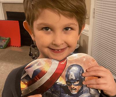 Miles David Tillman, a young boy holding a superhero kevlar balloon