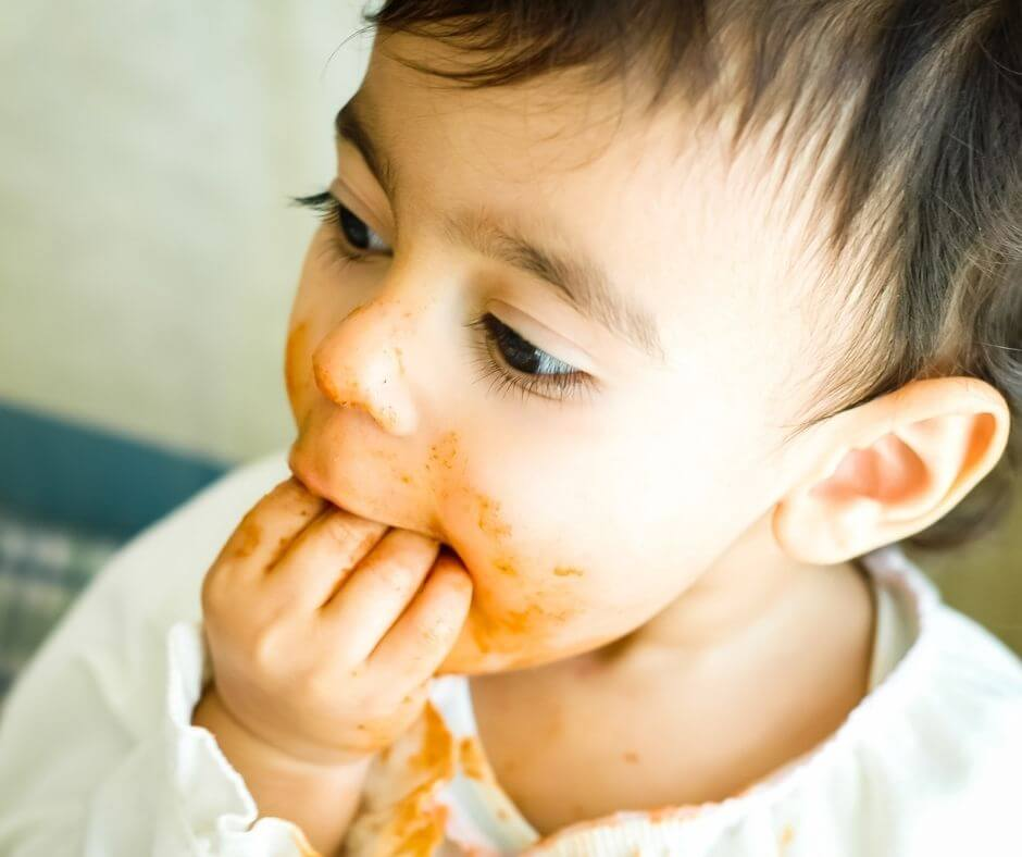 child stuffing food in mouth